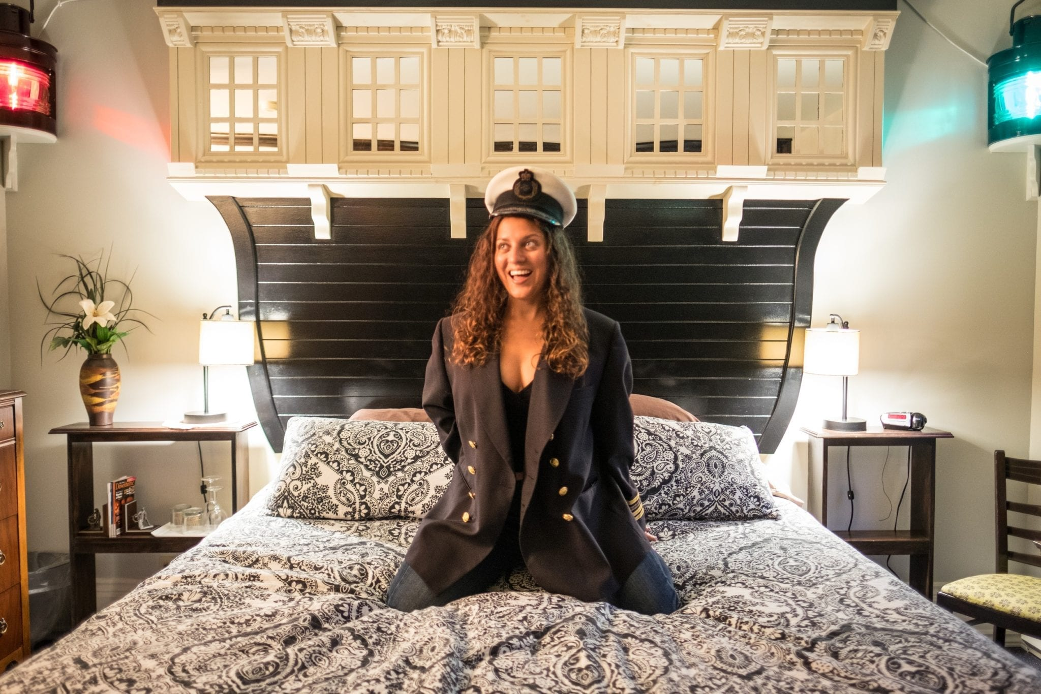 Kate does a split on a bed with a headboard that looks like the front of a ship. Nautical lights, red and green, glow behind her. She wears a captain's hat and blazer.