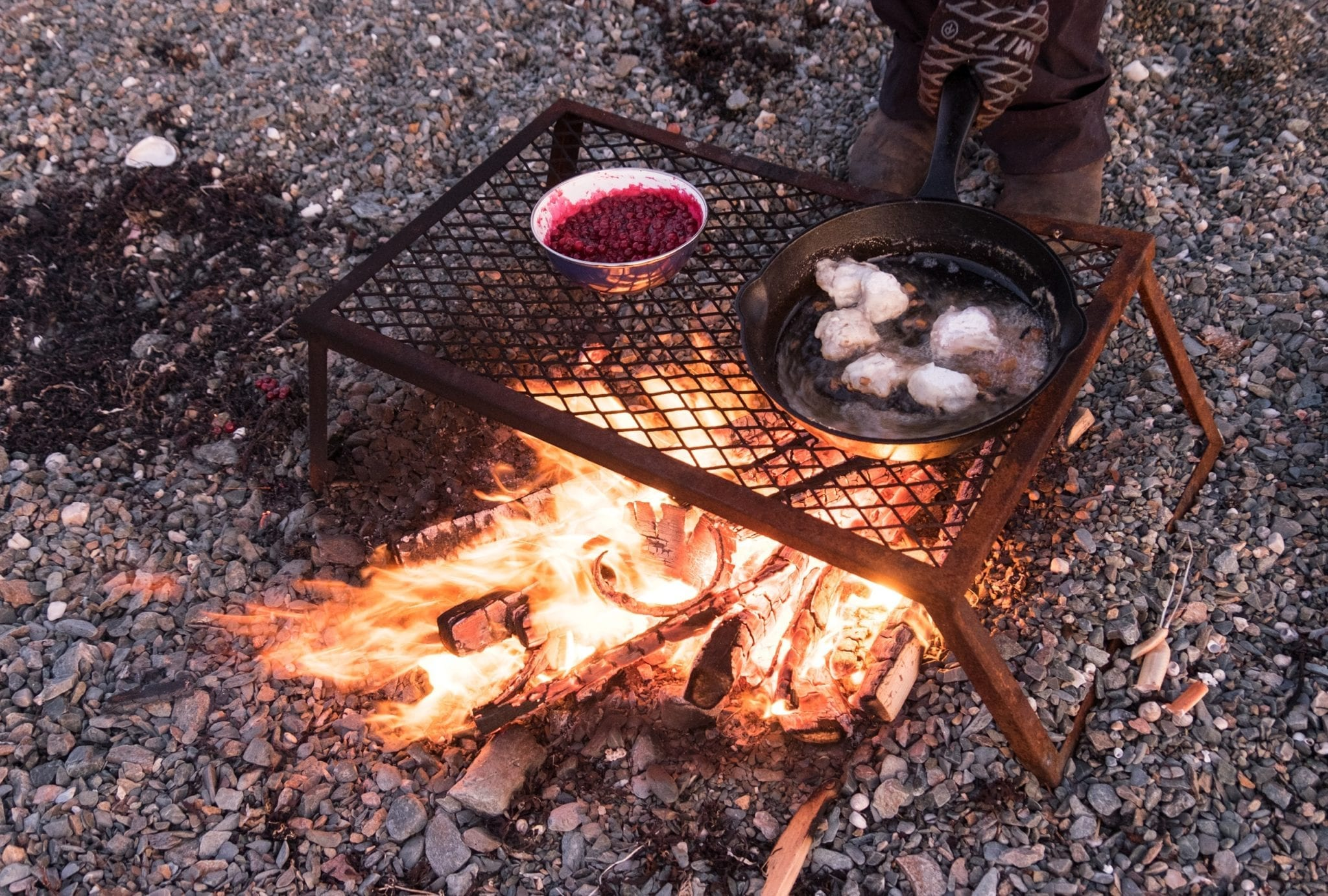 A campfire with a grill on top: cod tongues cooking in a skillet on one side, berries cooking in a dish on the other.