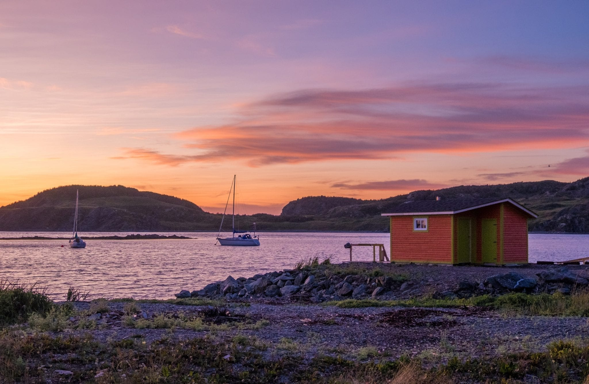 A sunset with a light purple sky and pink and dark purple clouds, in front of a red fishing hut and a sailboat