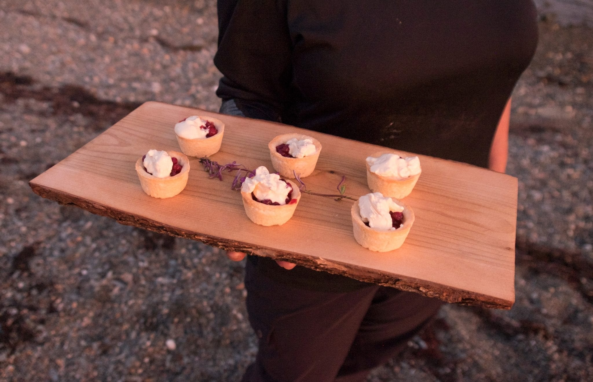Crystal holds a wooden slab topped with six tiny tartlets filled with partridgeberries and topped with cream.