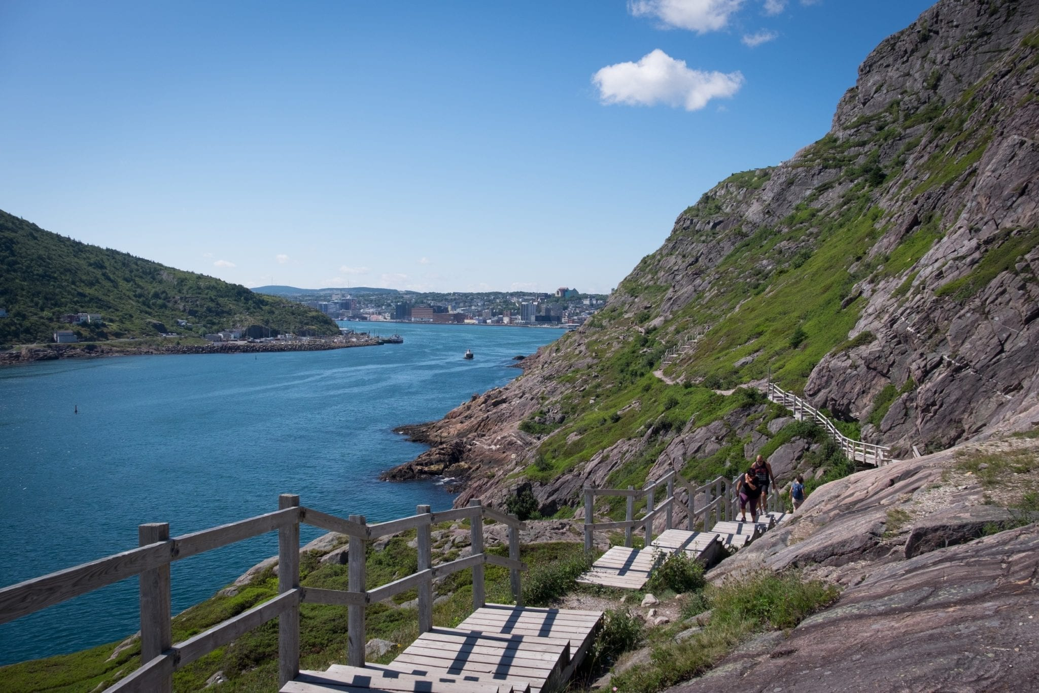 A hiking trail with wooden stairs leading up rocky cliffs in front of the bright blue bay in St. John's, Newfoundland.