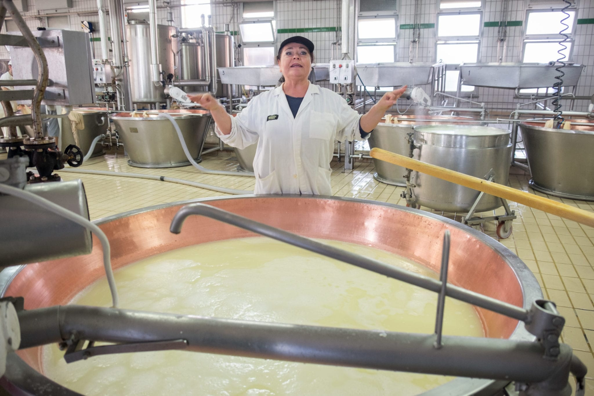 A woman in a smock stands in front of a liquid vat, spreading her arms and talking about cheese.