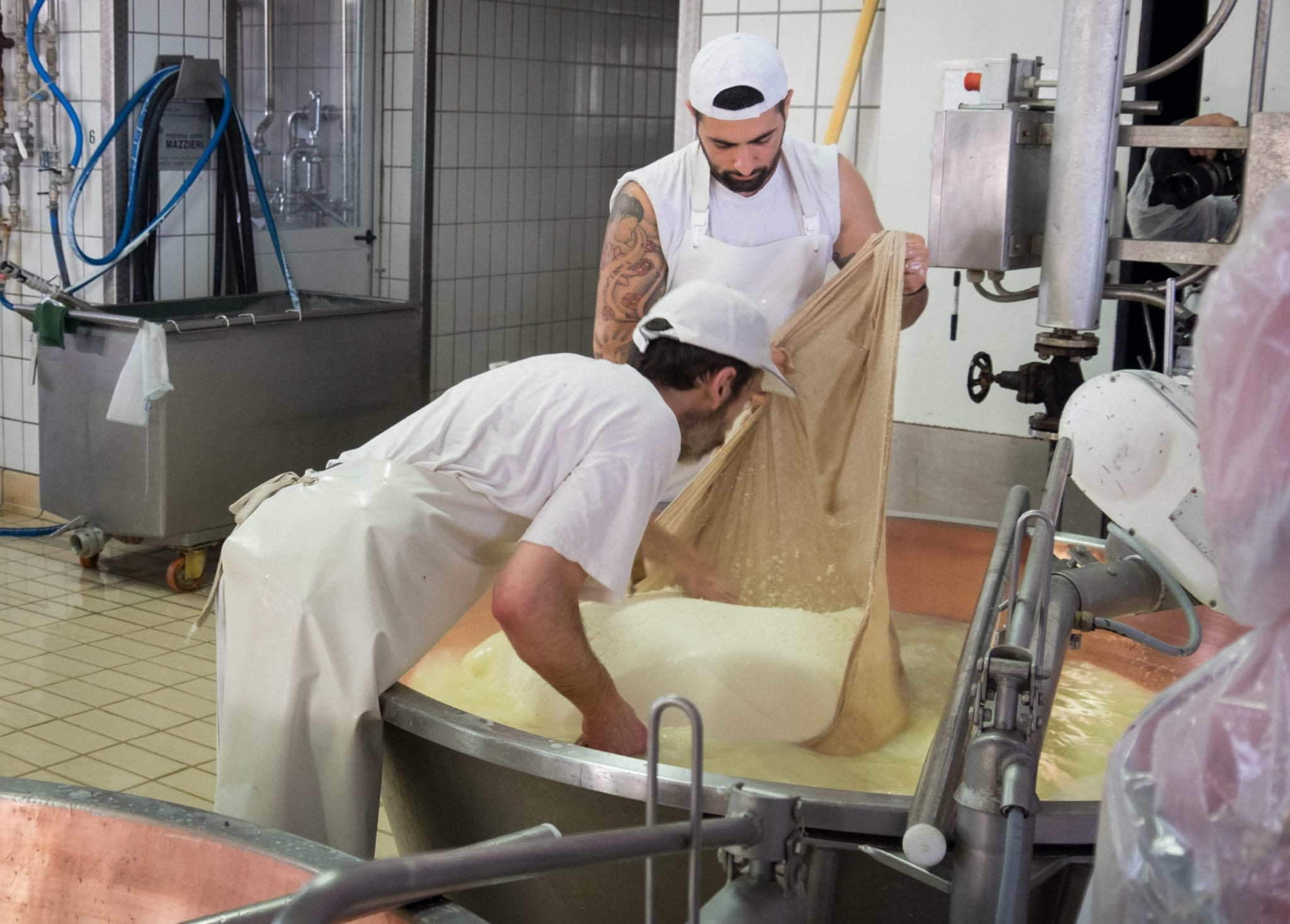Two men, one very handsome and covered with tattoos, hold a cloth with a block of cheese on top in the vat.