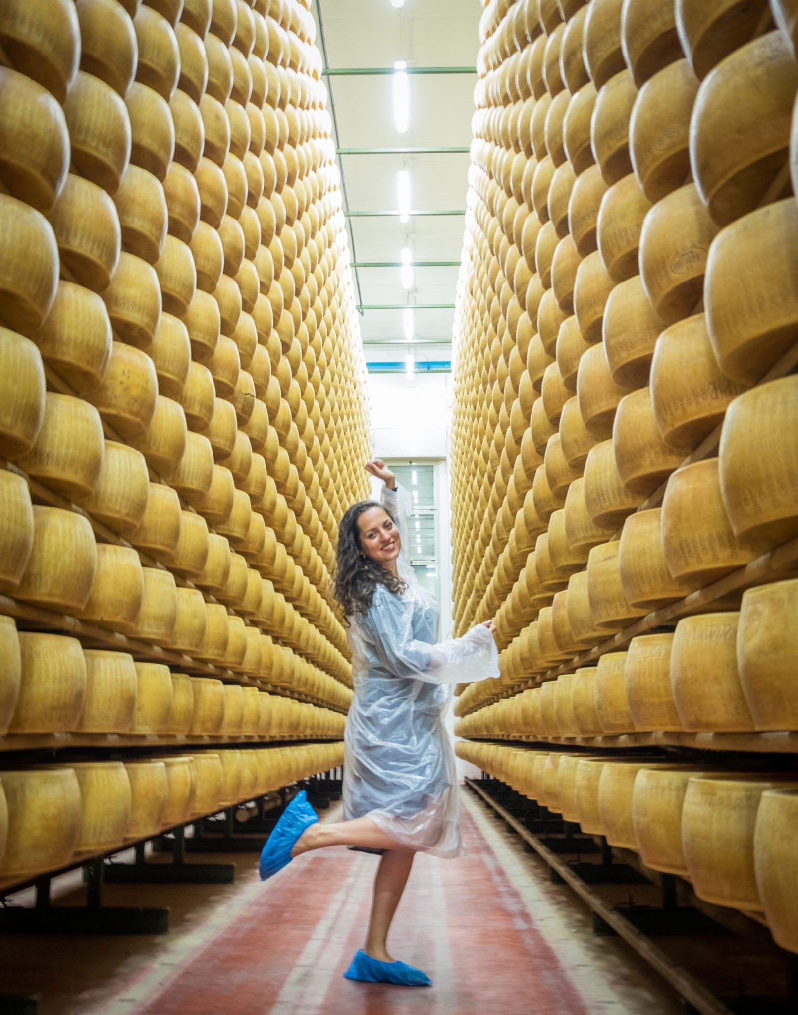 Kate poses with one foot in the air in the middle of the aisle in the cheese factory, surrounded by rows and rows of cheese.