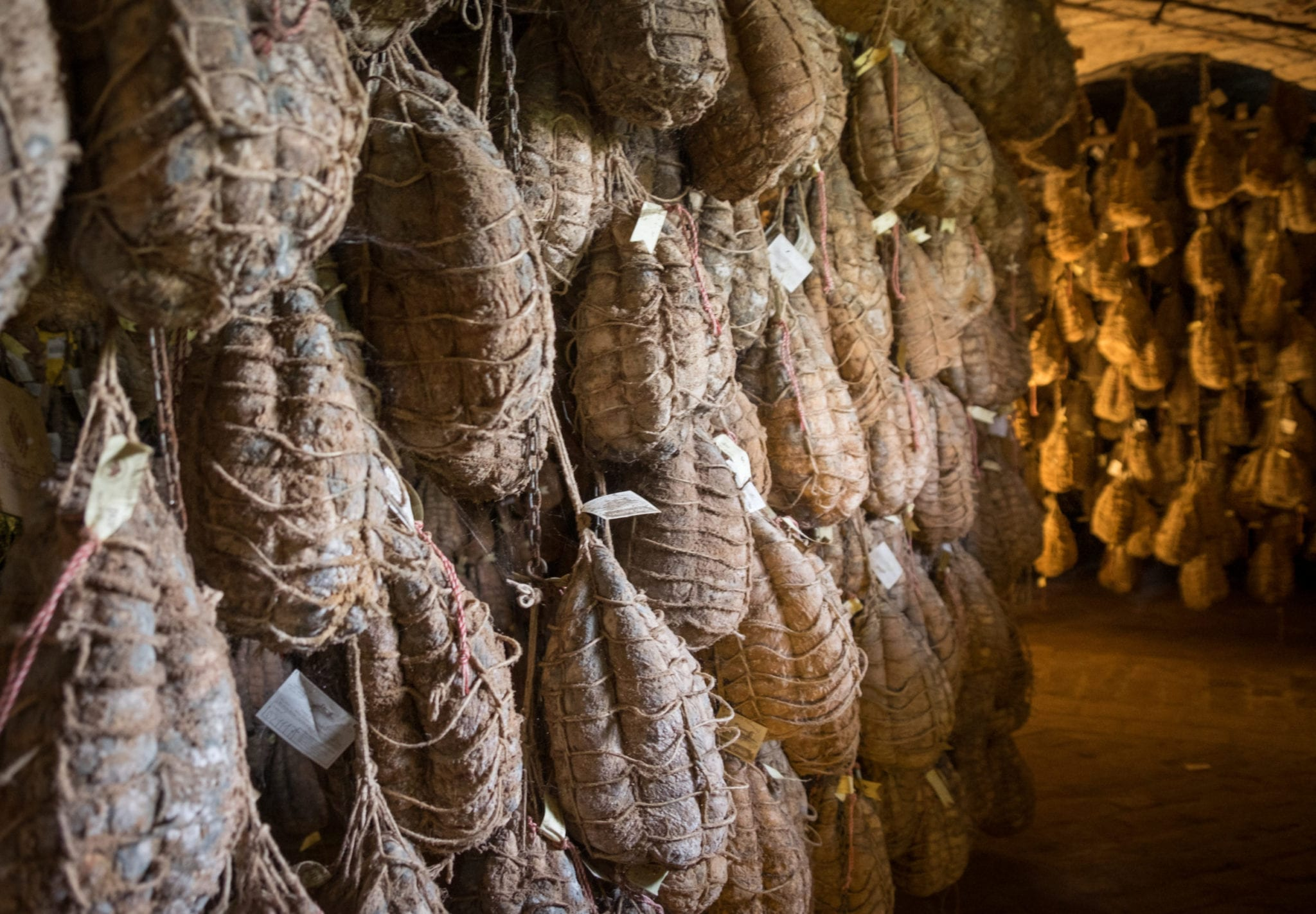 Racks of Culatello hams hanging in a cellar.