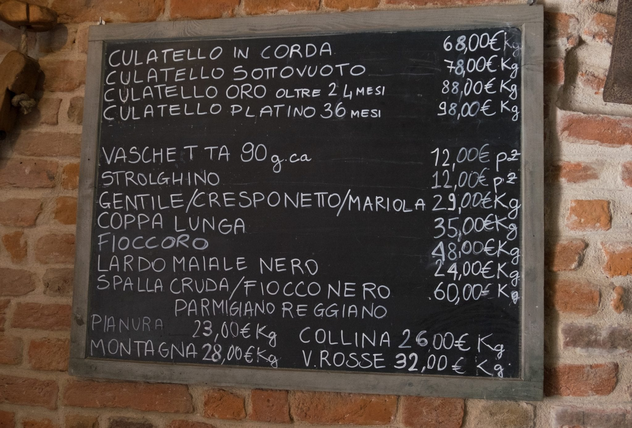 A blackboard with the prices of culatello written on them, starting at 68 euros per kilogram.