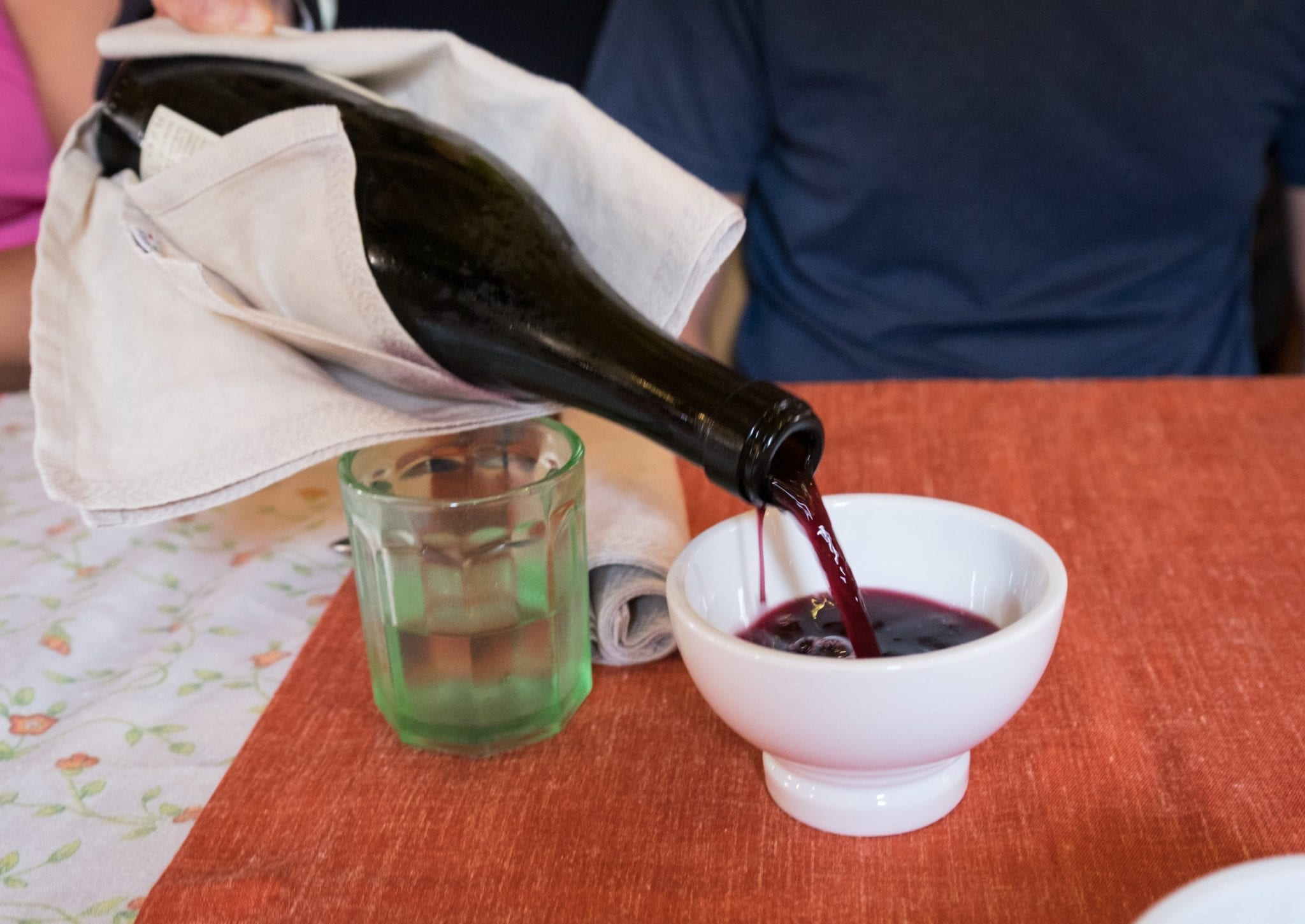 A bottle of red wine being poured into a small white bowl for drinking.