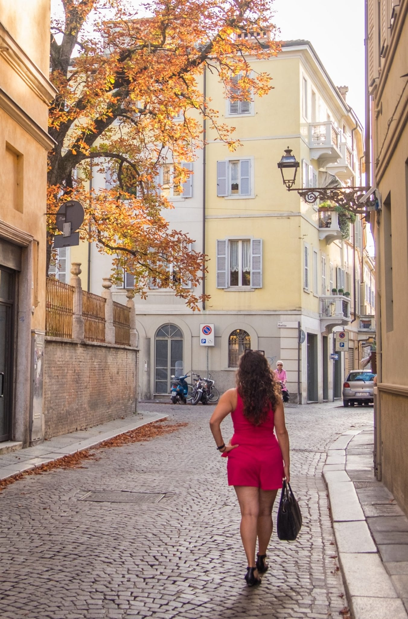 Kate wears a short hot pink romper and stands on a cobblestoned street in front of a yellow building and a tree with autumn leaves.