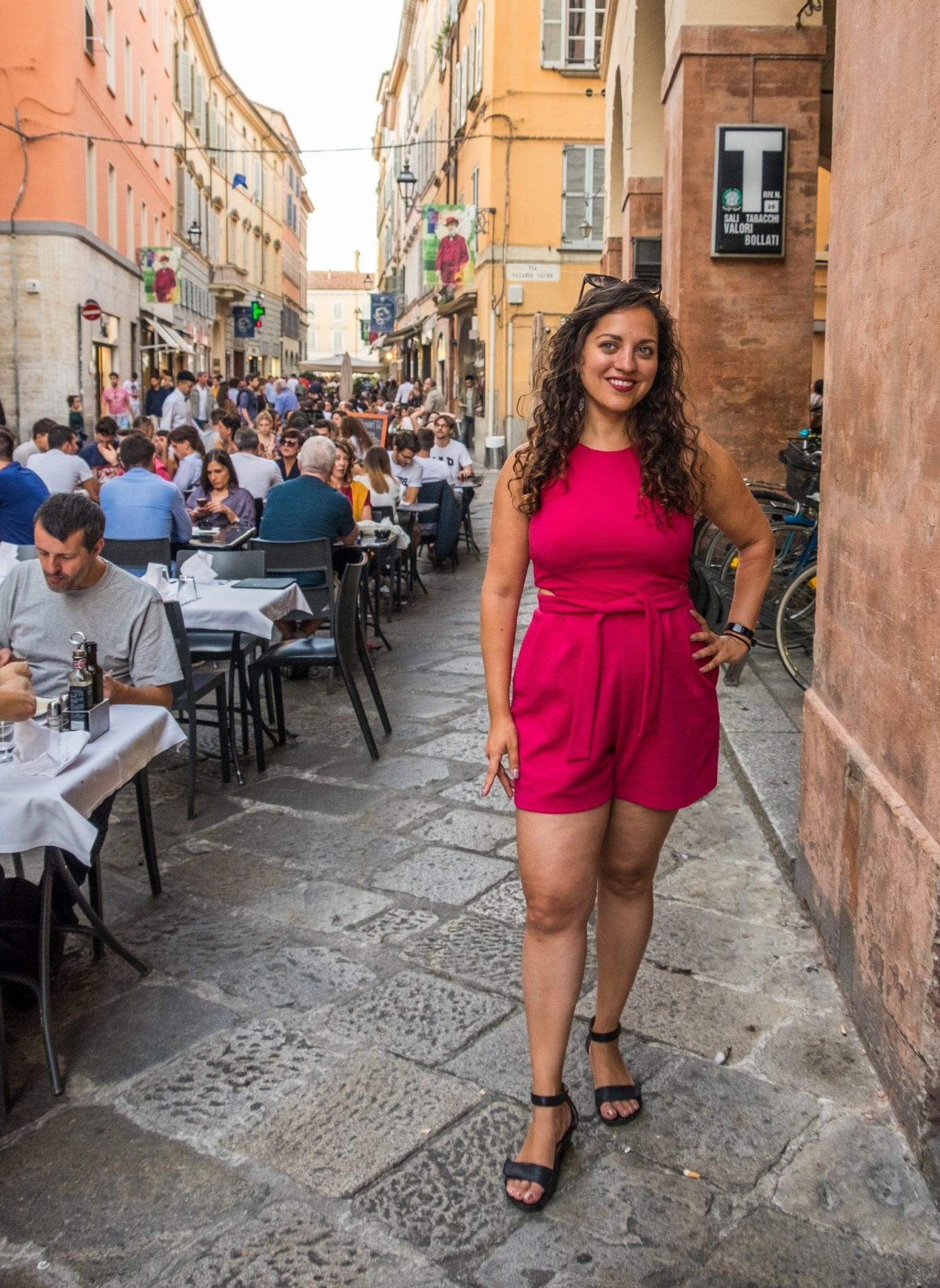 Kate wears a hot pink romper and stands on the street in Parma, next to people sitting down eating at outdoor tables, yellow and pink buildings behind her.