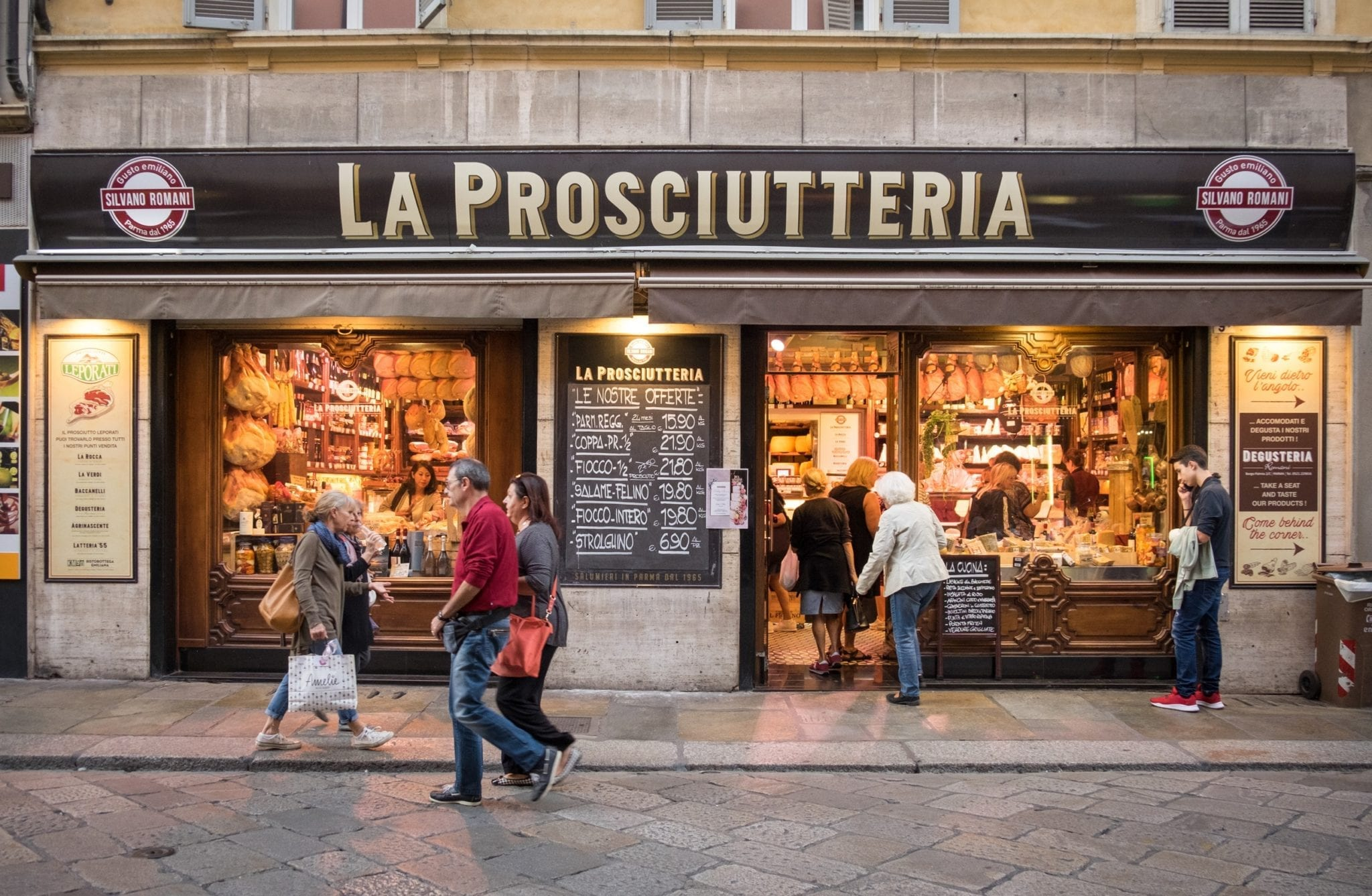 "A butcher shop reading ""La Prosciutteria"" with people walking in front of it in Parma, Italy."
