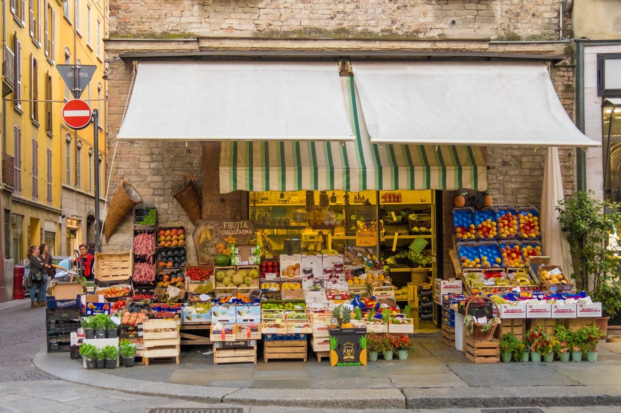 A fruit stand brimming with piles of fruits and vegetables in Parma, Italy.