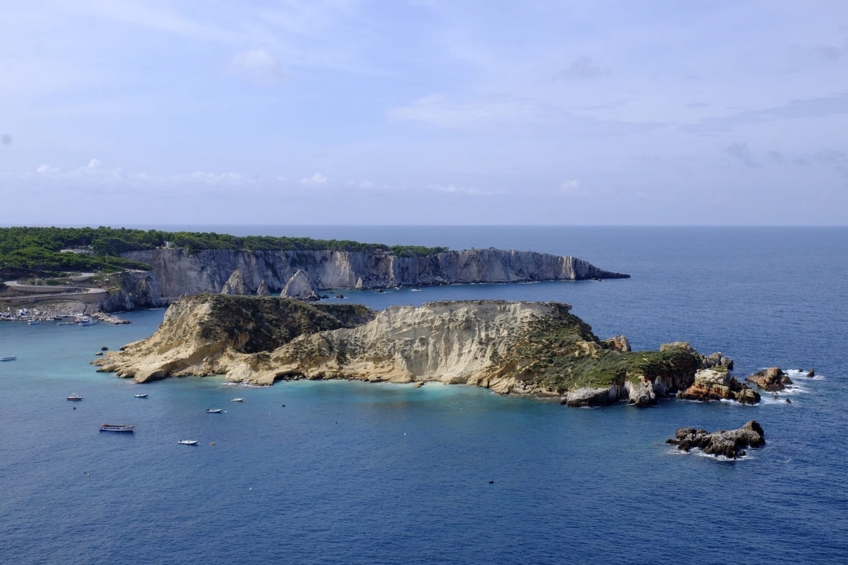 A view over two of the Tremiti Islands -- a rocky, uninhabited island, covered with sand and grass, rising out of the bright blue sea. Rowboats in the water in front of the island.