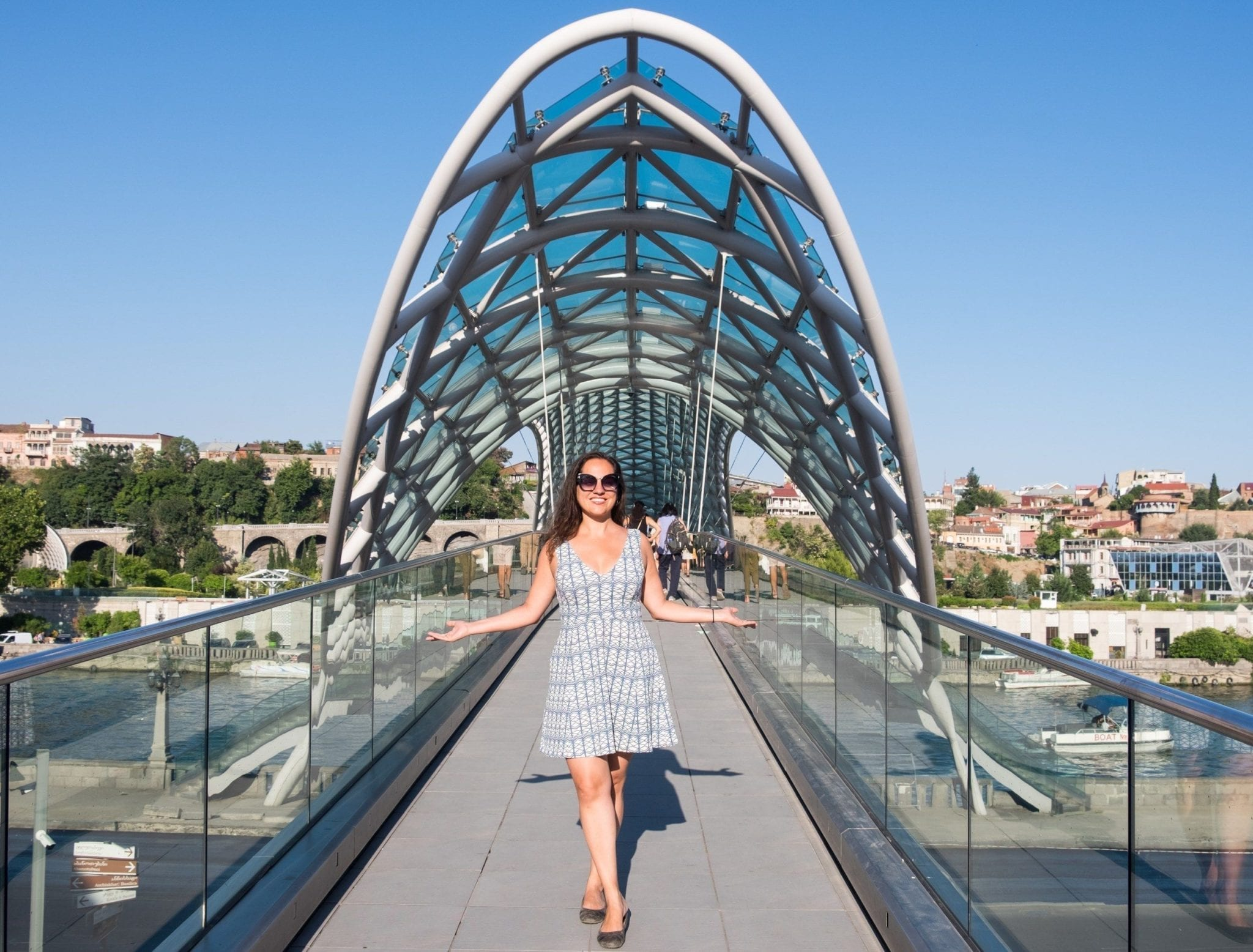 Kate stands in front of the Peace Bridge in Tbilisi, Georgia, which is modern and a grid-like oblong shape interspersed with green-blue panels of glass. Kate wears a white dress with a white and green and blue geometric pattern that looks similar to the bridge.