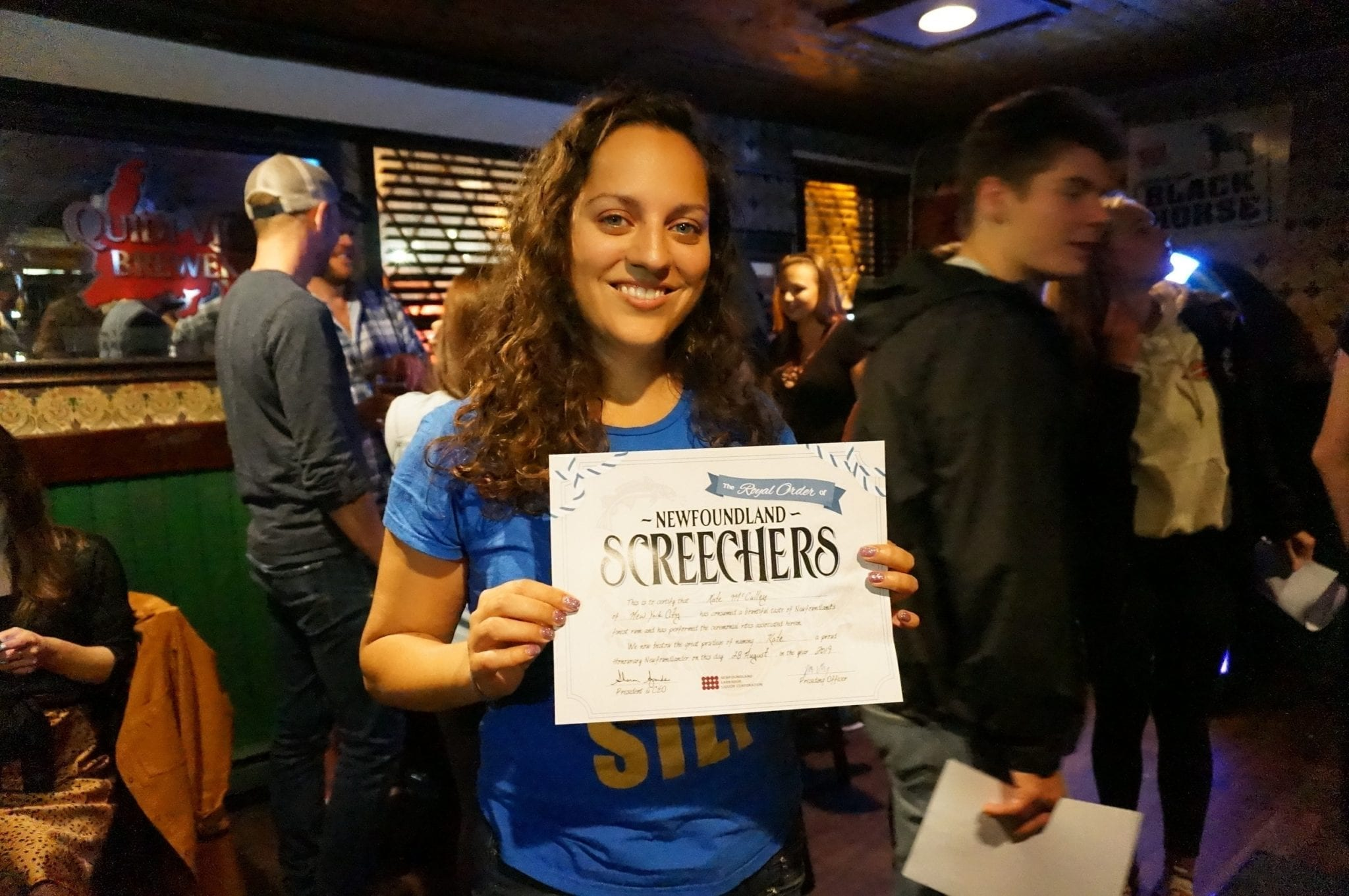 "Kate stands in a bar holding a certificate that says ""SCREECHERS""."