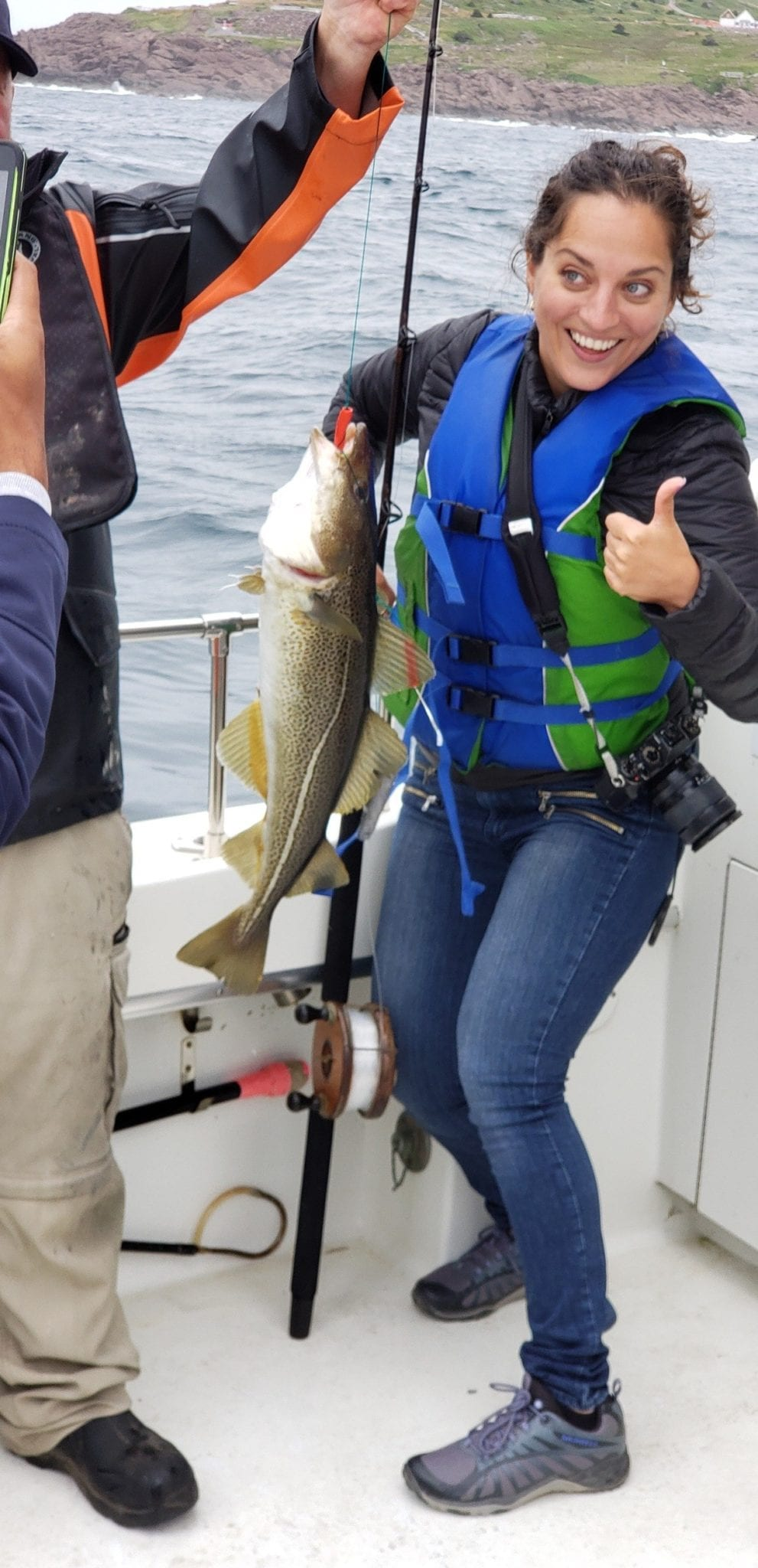 Kate holds up a fish roughly from her chest to her knees and gives a thumbs up.