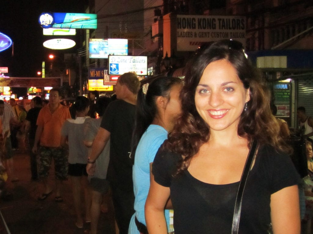 A young-looking 26-year-old Kate stands on Khao San Road in Bangkok, filled with neon signs and crowds. She has a huge smile.
