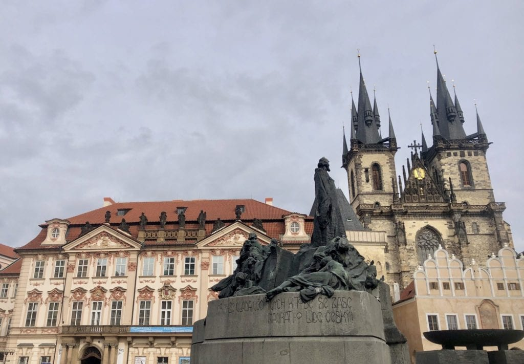 A statue in front of a church tower and crenellated building on Old Town Square in Prague.