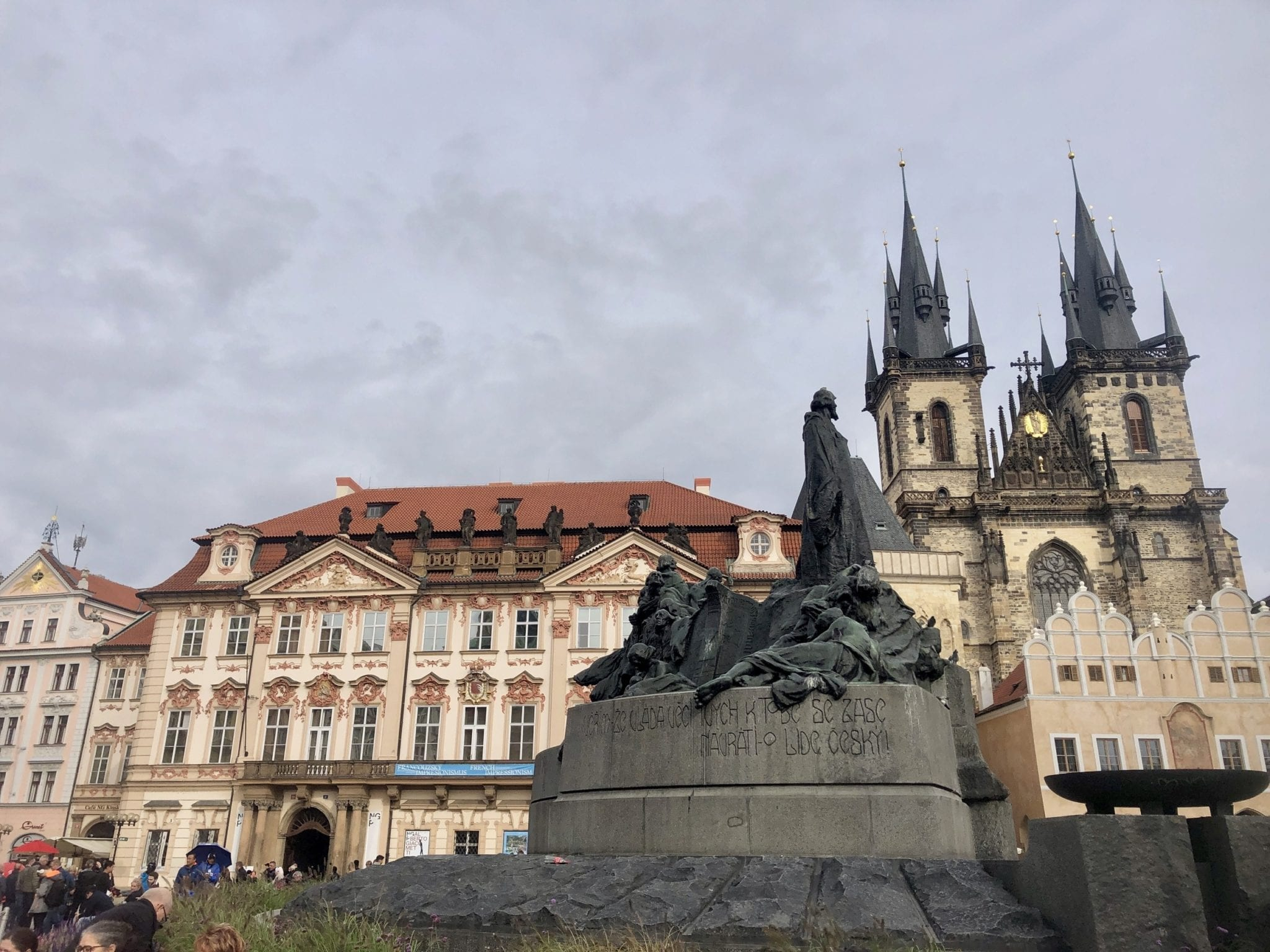 A scene from Old Town Square in Prague: a statue of soldiers in front of a cream-colored building with an orange roof and two church towers. Shot from below because THIS SQUARE IS FULL OF THOUSANDS OF TOURISTS.