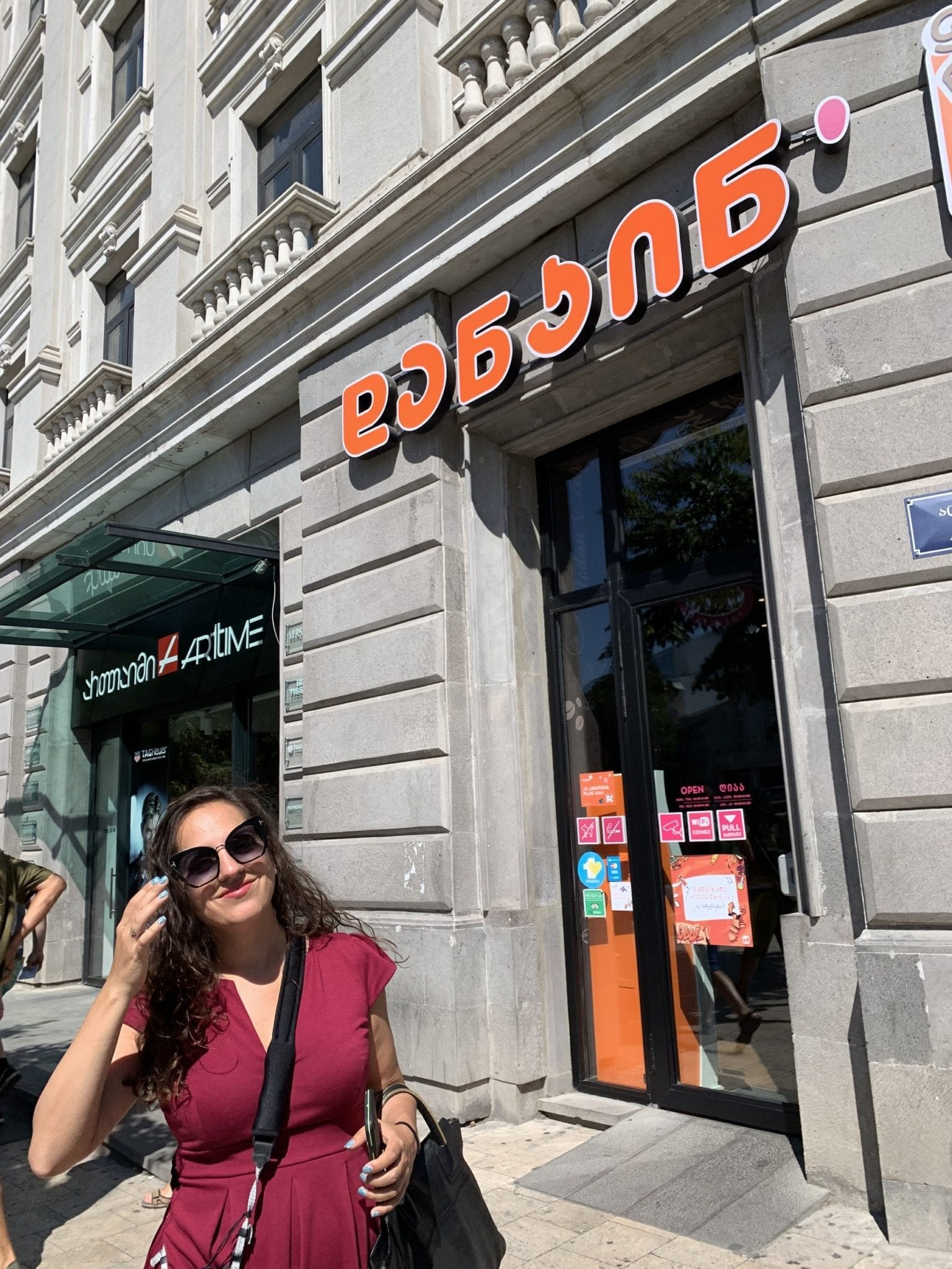 Kate smiles while standing in front of what looks like a Dunkin Donuts, with the name written in Georgian script.
