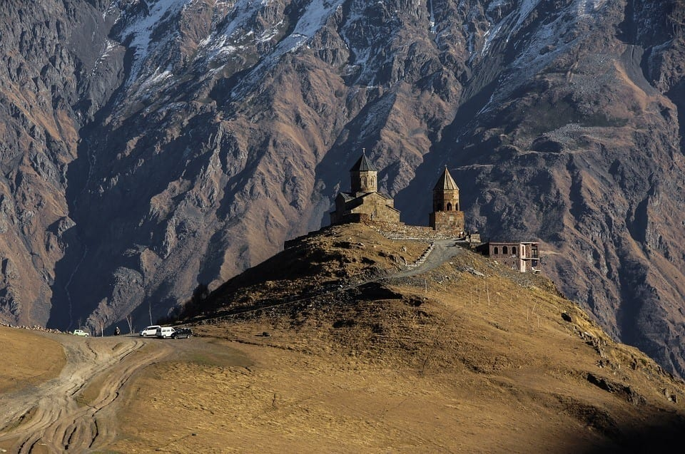 The church of Kazbegi, perched on a hill with a mountain backdrop behind it.