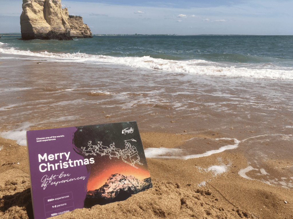 "A Tinggly gift card reading ""Merry Christmas"" on the beach, next to the water."