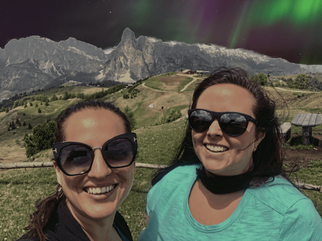 Kate and Cailin standing under a fake Northern Lights view in the Dolomites