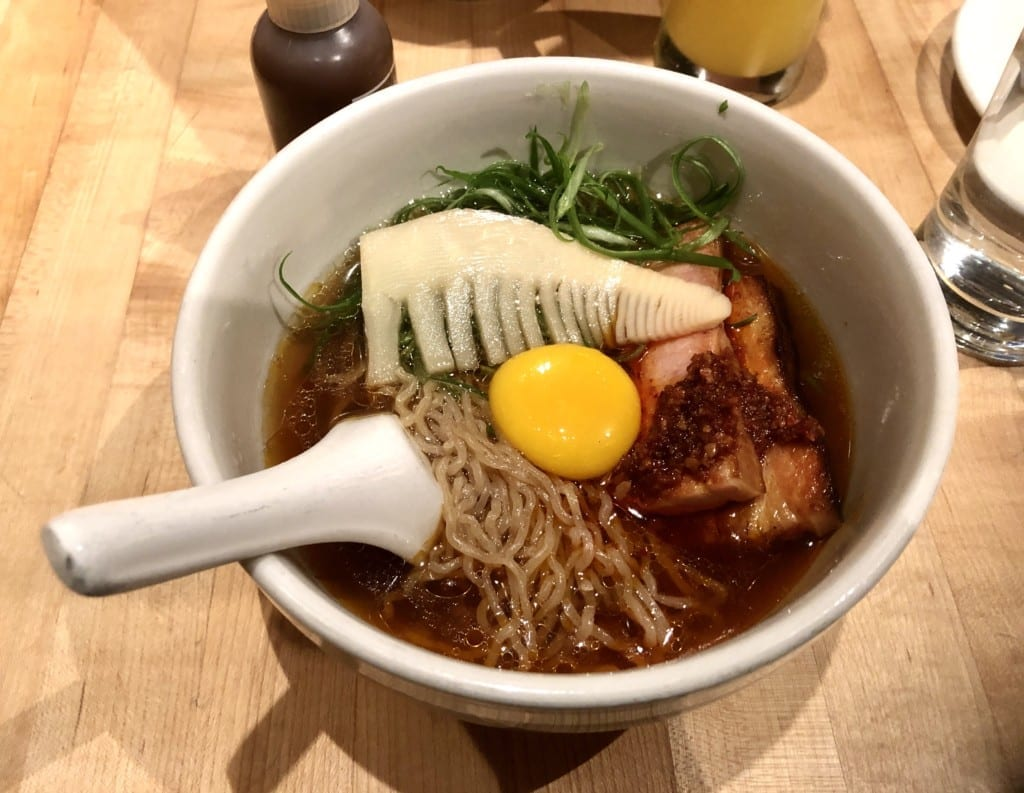 A bowl of ramen with noodles, pork belly, bamboo, and an egg yolk at Momofuku Noodle Bar.
