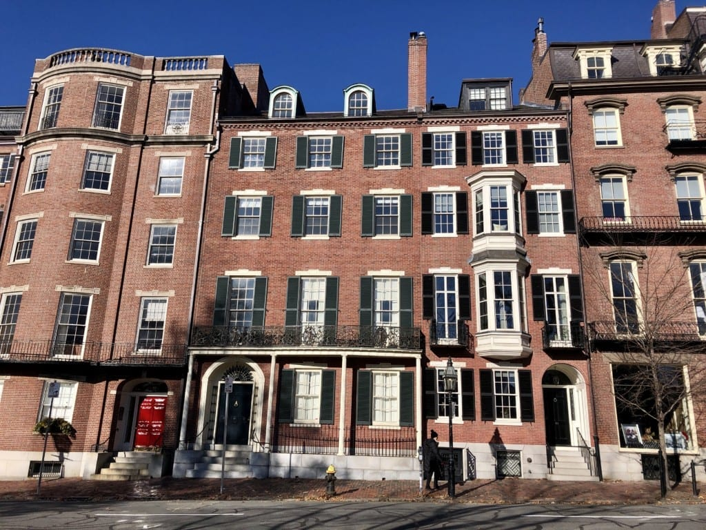 A row of fancy Beacon Hill brownstones in Boston beneath a bright blue sky.