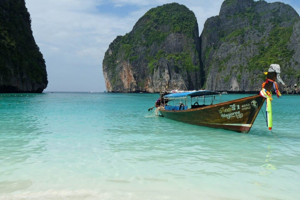 A single Longtail boat on the turquoise water with Koh Phi Phi's cliffs rising around.