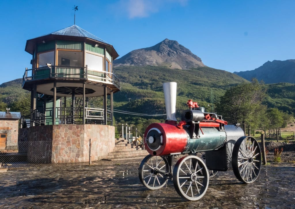 A bright red old-fashioned steam train engine in front of a mountain in Ushuaia.