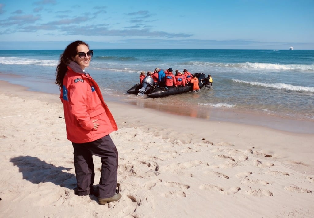 Kate wearing a red coat and standing on the beach in Sable Island, turning her head back to face the camera with a grin, as a zodiac filled with passengers leaves the island.