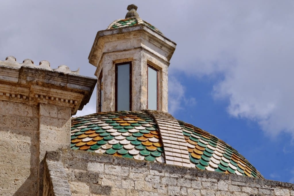A church dome topped with green, orange, and white tiles in Ostuni, Italy.