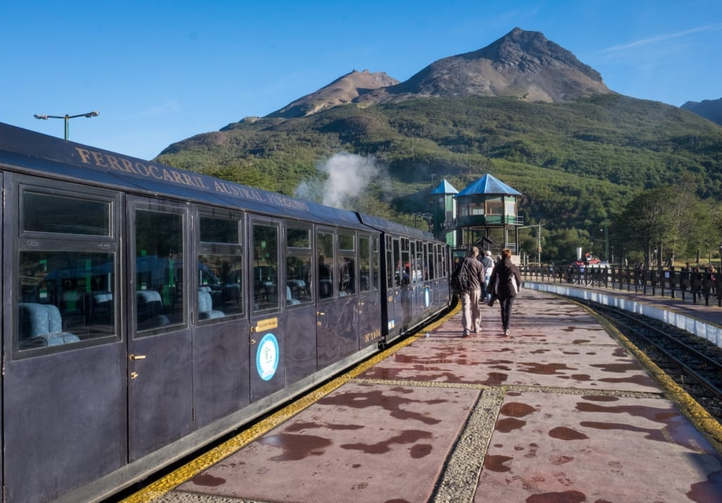 A silver passenger train picks up passengers in the mountains.