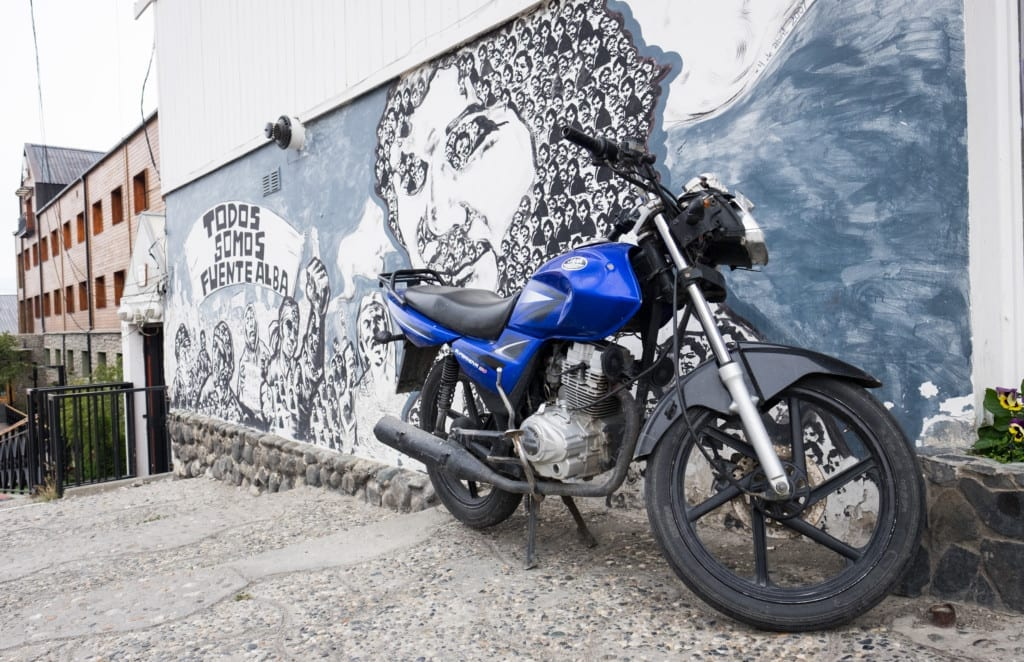 A blue motorbike in front of black and white street art in Ushuaia.