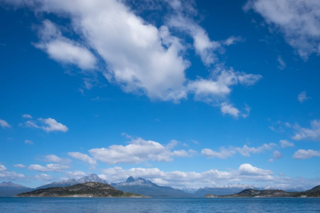 Mountains along the Beagle Channel, a bright blue sky with fluffy clouds overhead.