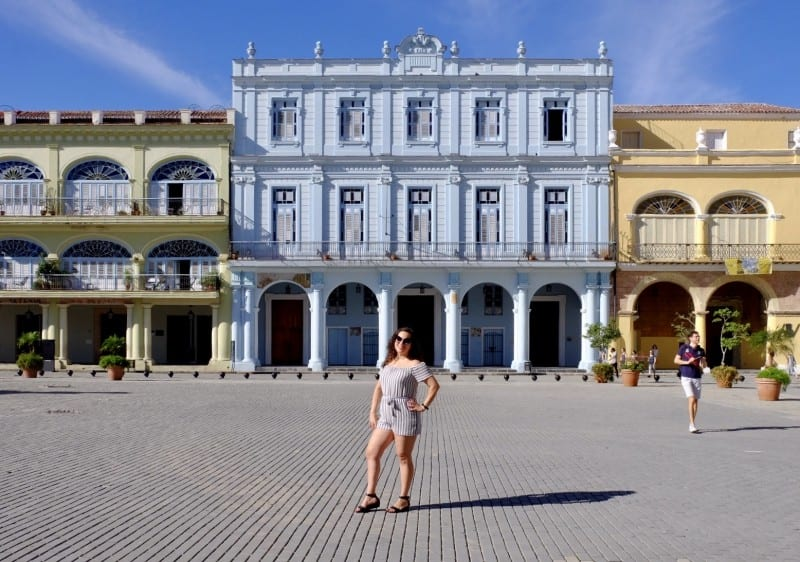 Kate stands on a plaza in front of blue and yellow colonial buildings in Havana.
