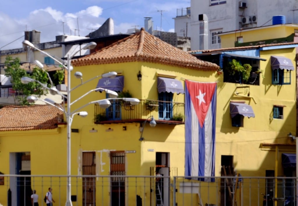 A yellow building with a giant Cuban flag hanging from a window.