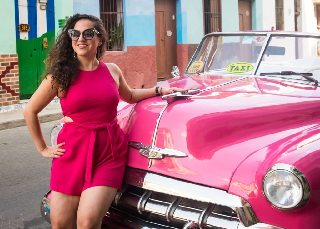 Kate wears a bright pink romper and stands in front of a bright pink classic car in Havana.