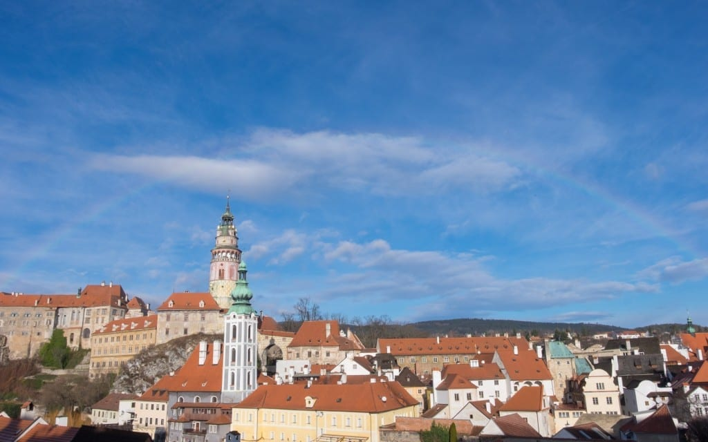 A rainbow in the sky over the orange-roofed buildings of Cesky Krumlov, Czech Republic