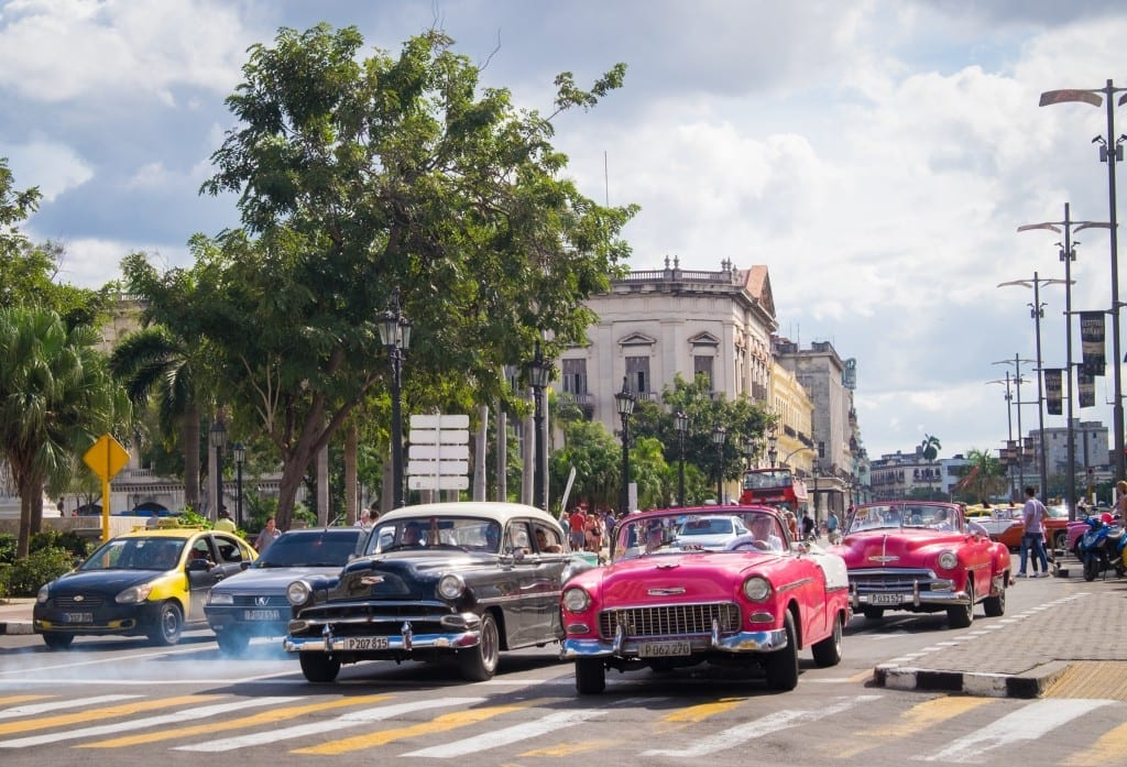 Classic cars at an intersection in Havana, clouds of exhaust behind them.