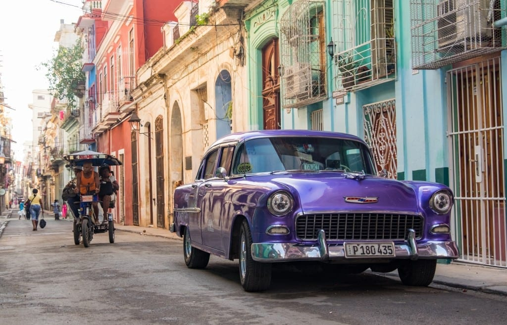 A shiny purple classic car on a brightly colored Havana street.
