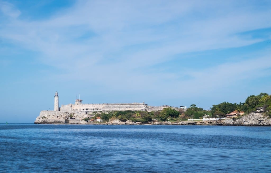 A view of the lighthouse on the ocean in Havana underneath a blue sky.