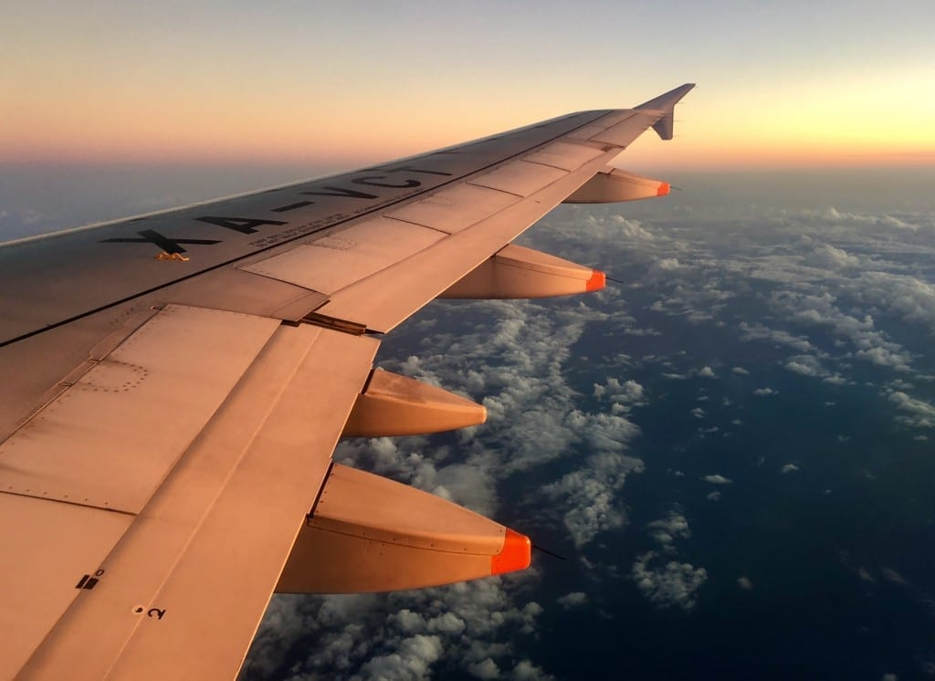 A plane wing at sunset, over a dark cloudy sky.