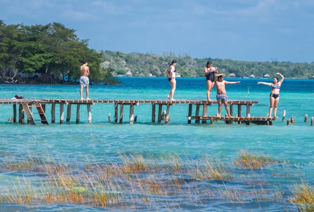 A group of friends having fun and posing on a dock on top of bright neon water in Bacalar.