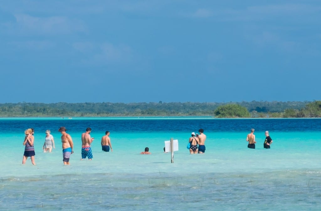 People standing in the shallow water of Bacalar. You can see the colors change from pale aquamarine to bright turquoise, bright blue and dark inky navy.