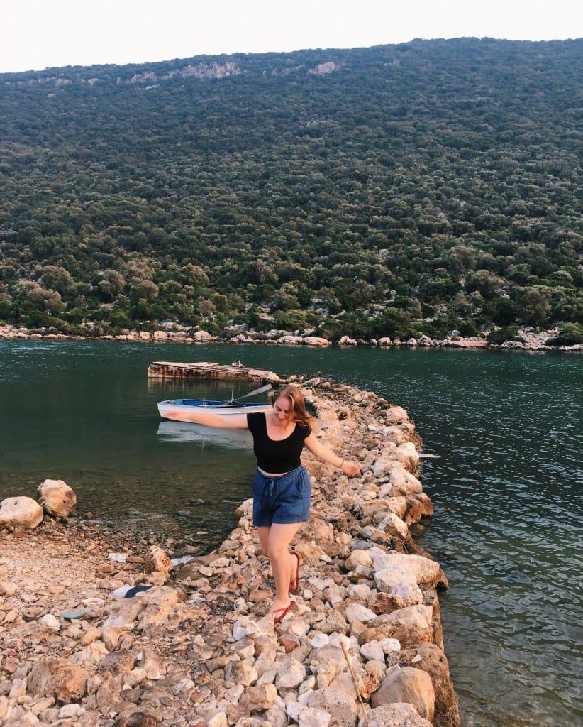 Katie balancing on a rocky jetty in the dark green Mediterranean.