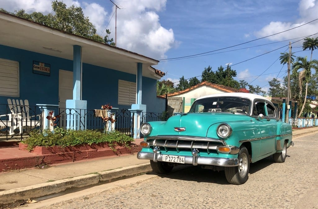 A bright turquoise classic car parked on a street in front of a blue home in Viñales, Cuba.
