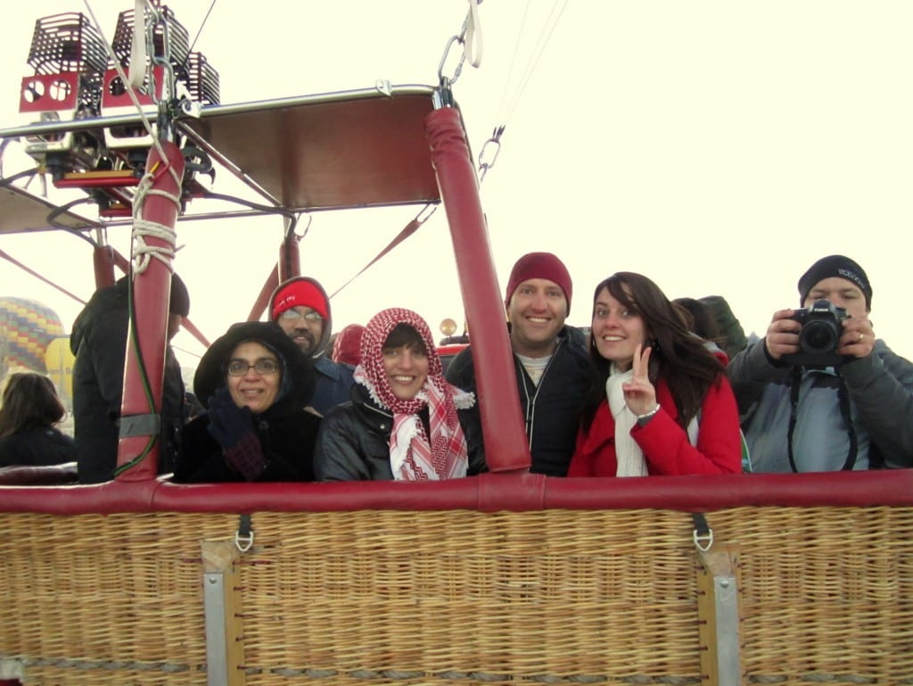 Kate and five other people smiling for the camera in the basket of a hot air balloon.