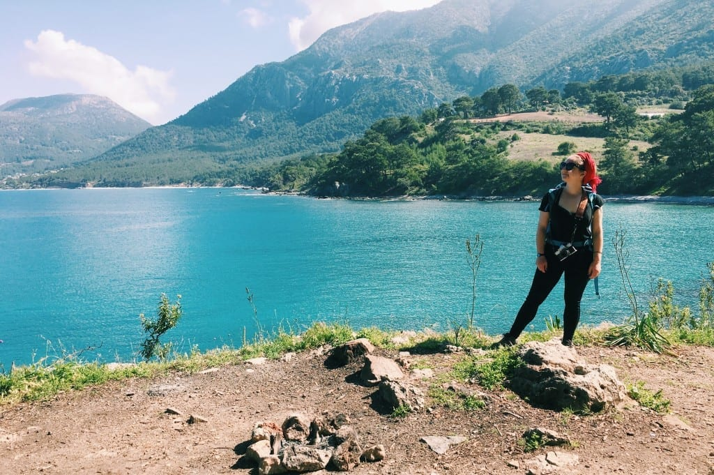 Katie standing on a hiking trail near the teal water of the Mediterranean om the Lycian Way.