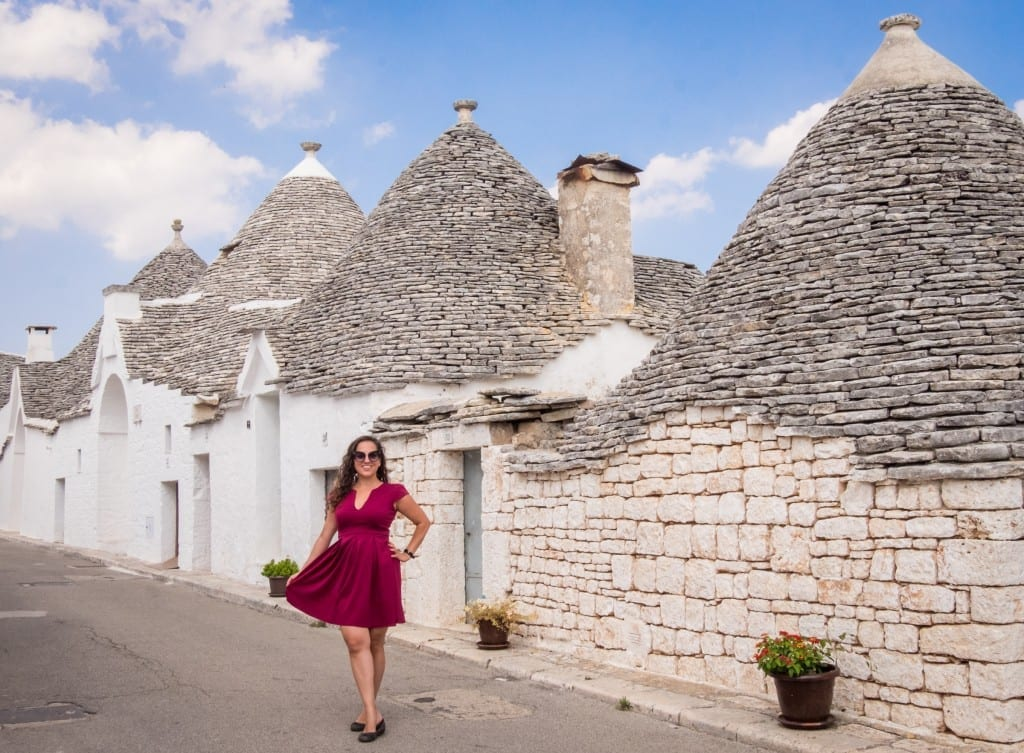 Kate wears a red dress and poses, holding it open, in front of the white conical trulli homes of Puglia.